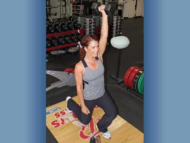 Madia performs a lunge with overhead press.