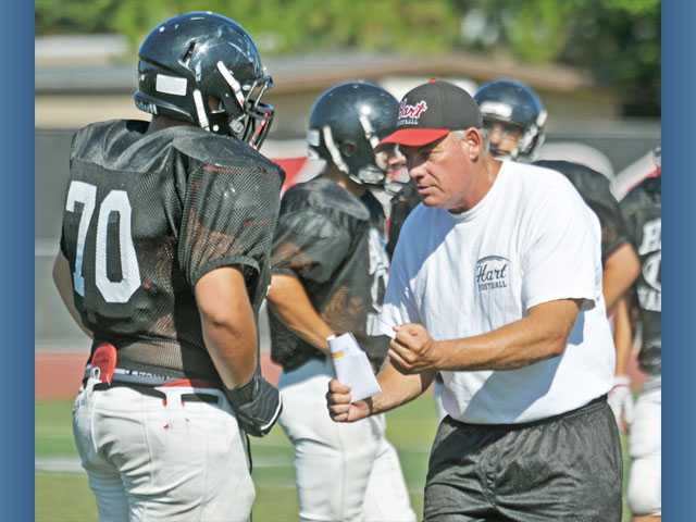 Hart football head coach Mike Herrington, right, coaches up offensive lineman John Perkins during practice on Thursday.
