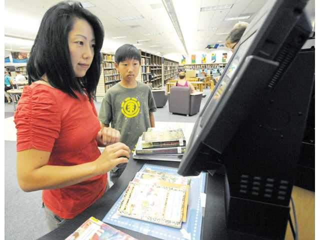 Sandy, left, and Brandon Yu, of Westridge, check out materials with new self-service kiosks at the Santa Clarita Public Library's Valencia branch