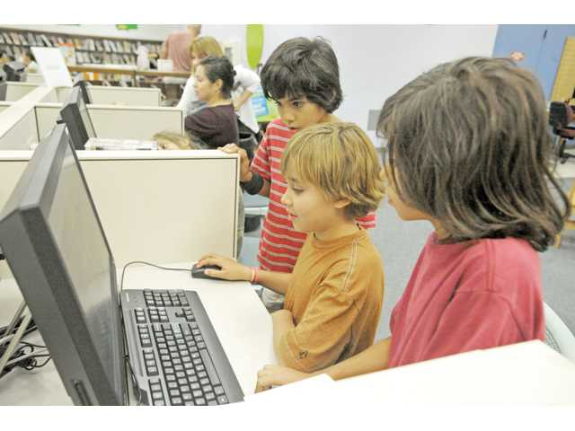 From left, Justin Cubano, 9; Ravi Johnson, 10; and Jon-Michael Cubano, 11, gather around one of several new self-contained public computers in the children's area of the Santa Clarita Public Library's Valencia branch on Wednesday.