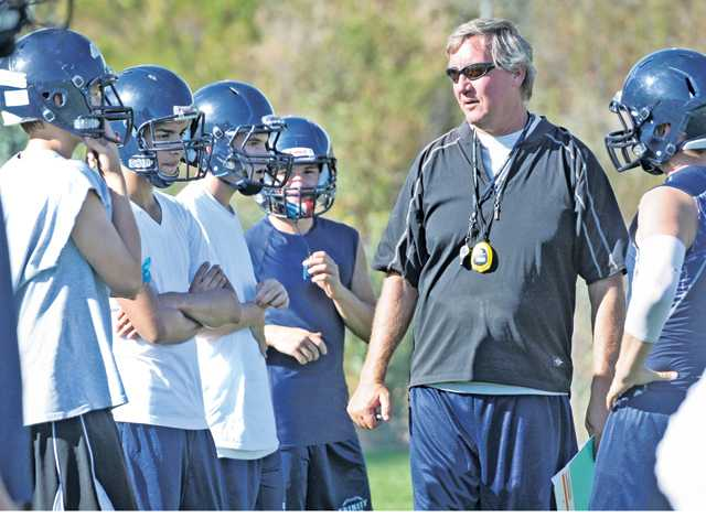 Trinity football head coach Mike Buchanan, second from right, talks to the team during practice at Trinity Classical Academy on Wednesday. Buchanan, who was an assistant last year, is entering his first season as head coach.