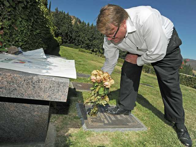 Chan Reader removes flowers from his son Sean's gravestone, from a space that usually houses a bronze vase, at Eternal Valley Memorial Park in Newhall on Monday.