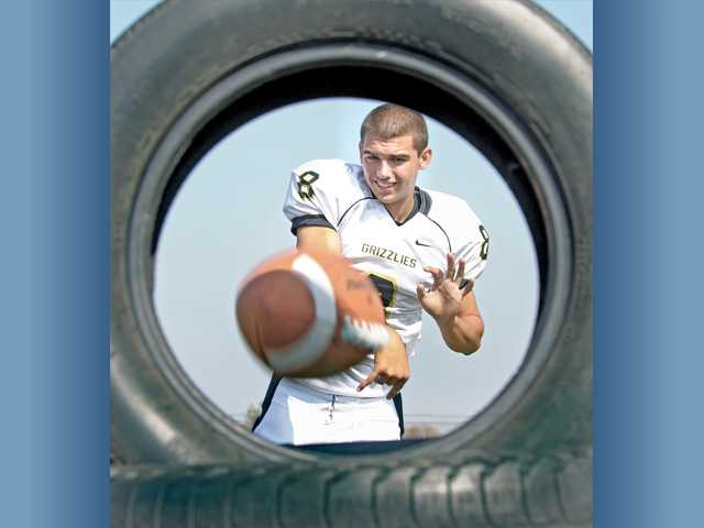 Golden Valley QB Reid Soliman throws a football through a tire at a Grizzly football practice.  The senior quarterback was thrust into the starting role his sophomore season and forced to learn on the fly.