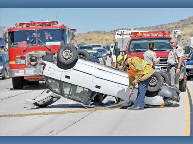 A firefighter cleans debris as California Highway Patrol officers investigate the scene of a solo car crash on southbound Highway 14, south of Escondido Canyon Road, in Agua Dulce on Wednesday. The female driver of the Geo Metro sedan escaped from the vehicle with minor injuries, authorities said on the scene.