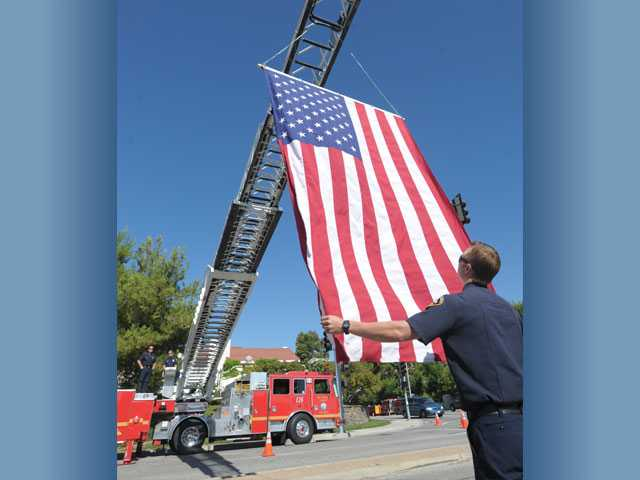 "Josh Berry, a firefighter from Fire Station 126 in Valencia, guides the flag as it is raised over the intersection of Stevenson Ranch Parkway and Poe Parkway, at the 10-year remembrance ceremony in honor of Deputy Hagop ""Jake"" Kuredjian, in Stevenson Ranch on Wednesday."