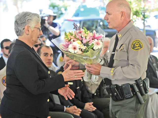 "Annie Kuredjian, left, mother of slain SCV Sheriff's Deputy Hagop ""Jake"" Kuredjian receives a bouquet of flowers from Santa Clarita Valley Sheriff's Station Capt. Paul Becker."