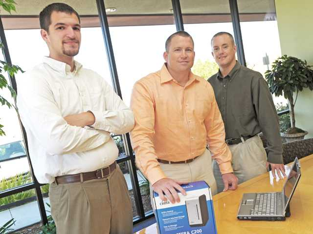 From left, Cloud49 staff members Zach Gates, Ryan Metro and Patrick Hamblin pose with a cloud-attached storage appliance at Mellady Direct Marketing in Santa Clarita.
