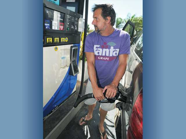 Scott Schweitzer, of Burbank, fills up his car's tank at the Arco station on Bouquet Canyon Road and Valencia Boulevard, in Valencia on Thursday.