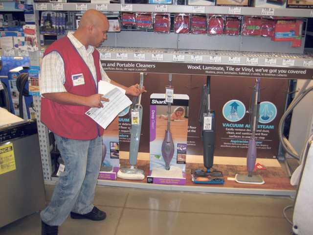 "Kyle Kennedy, appliance-sales specialist at the Saugus Lowe's, points out the Shark Steam Pocket Mop ($99.99), one of the newest innovations in small appliances. Predictions are that steam mops will soon be the next ""must-have"" small appliance."