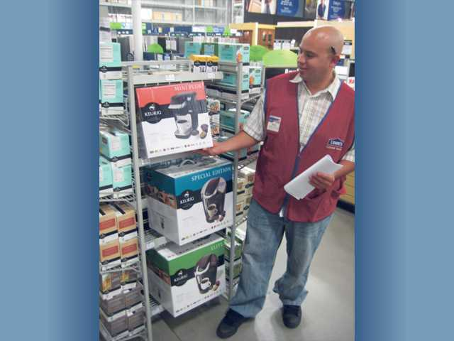 Kyle Kennedy, appliance-sales specialist at the Saugus Lowe's, points out a selection of Keurig coffeemakers. (Above left) The Keurig Elite B40 Brewer ($114.99) at Lowes.