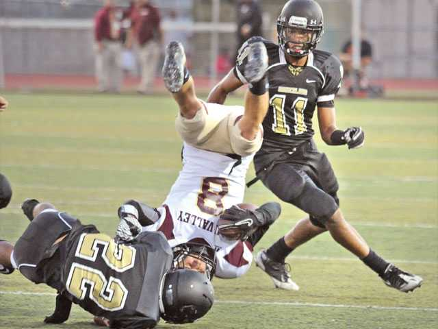 Golden Valley defensive back Christian Lozano (22) upends Simi Valley wide receiver Eric Pinkston (8) at Canyon High on Friday night. Golden Valley defensive back Isa Bey (11) looks on.