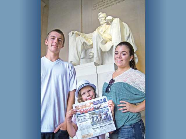 From left, Saugus residents Aidan, Viola and Alyssa Bartley pose with The Signal in front of the Lincoln Memorial in Washington, D.C.