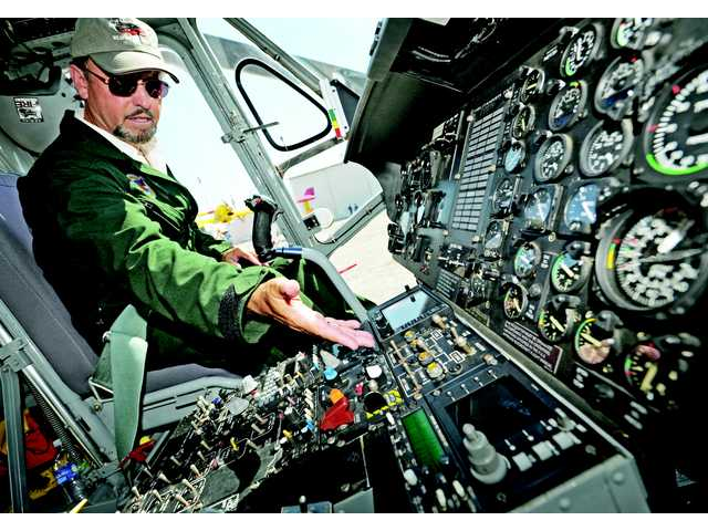 Command pilot Bob Hawthorne shows controls in the cockpit of an Erickson Air-Crane -Helitanker at Van Nuys Airport on Tuesday.