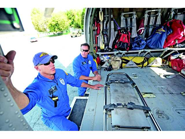Firefighter paramedics Fred Chavez, left, and Ron Massie describe the firefighting capabilities of the Sikorsky S-70 Firehawk helicopter, at Van Nuys Airport on Tuesday.