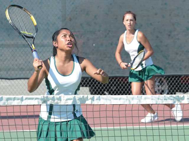 Canyon High doubles team member Paulette Alonsagay, left, eyes the tennis ball as teammate Brooke Licon shifts over at Canyon High on Tuesday.