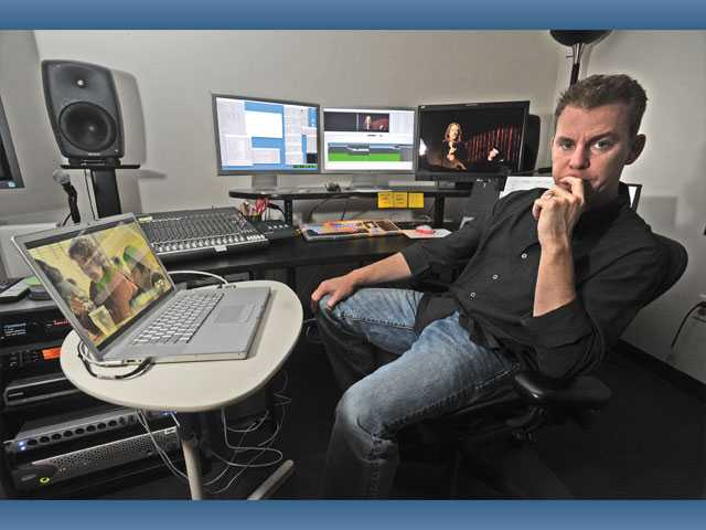 "Filmmaker Travis Fine, who wrote, produced and directed ""The Space Between,"" sits at a film-editing bay at a studio in North Hollywood on Wednesday."