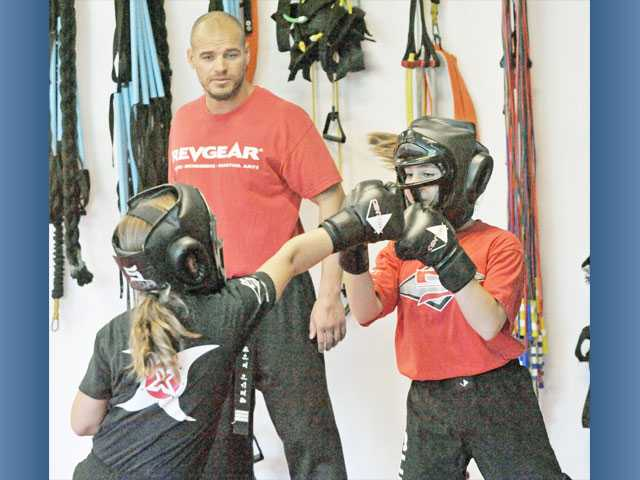 Instructor David Eastham, background, guides Jada Pearcy, 9, left, and Sonja Rossi, 12, through a tempo boxing exercise at Shin's Family Martial Arts Center in Valencia.