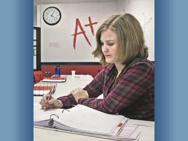 Emma Lee, 13, completes problems in her math workbook after school at Mathnasium in Newhall.