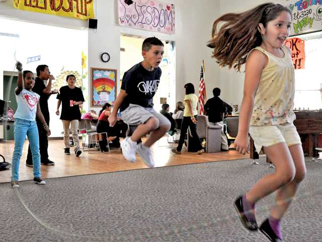 Rachel Espinoza, 8, right, and Zack Guarino, 8, middle, enjoy themselves while jumping rope at the Boys & Girls Club in Newhall.