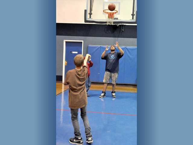 Jacob Hertan, 13, practices free throws with the help of assistant athletic director Tyrae Jones at the Newhall clubhouse.
