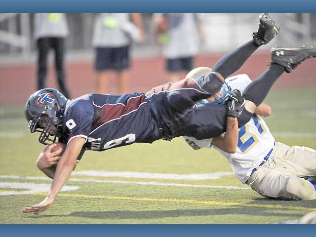 Trinity's Dakota Prochnow, left, dives into the end zone on Thursday at Valencia High as Calvary Baptist's Michael Kendall tries to make the tackle. Prochnow scored two touchdowns in the game.