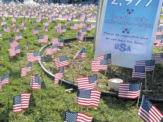 Saugus High School students walk past 2,977 American flags that students placed central quad amphitheater at Saugus High.