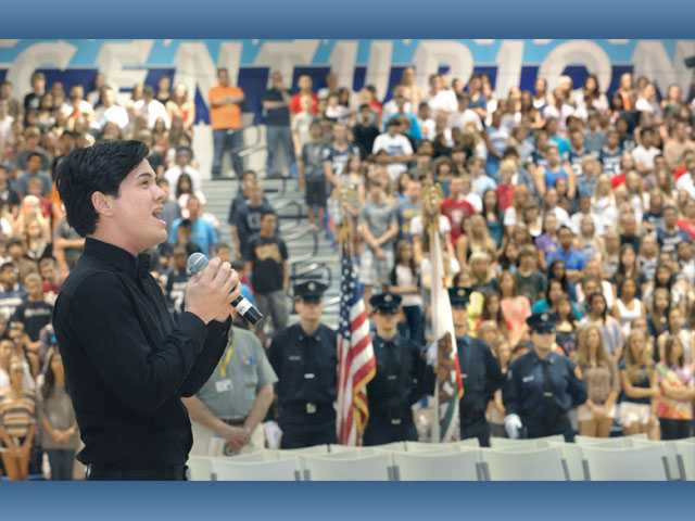 "Saugus High alumnus Michael Watanabe sings ""America the Beautiful"" before the Saugus High student body on Friday."