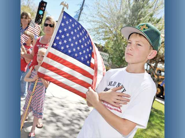 Andrew Jennerson, 11, of Santa Clarita, right, holds an American flag with his sister Rebecca Jennerson, 6, middle, and his mother, Roxanne Jennerson, 41, along a procession route for Army Spc. Rudy A. Acosta, on Orchard Village Road in Valencia.