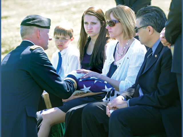 Brig. Gen. Gregg C. Potter, left,  presents the folded flag from the casket of Spc. Rudy A. Acosta to the Acosta's family at graveside services held at Eternal Valley Memorial Park on March 31.