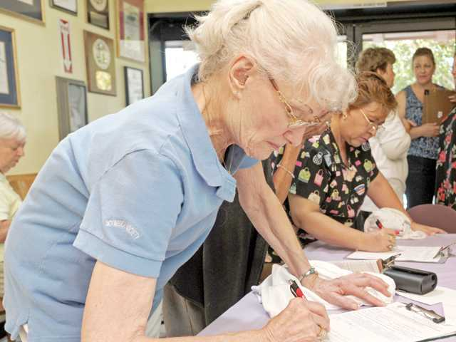 Mary Gallant, 87, writes a note expressing her gratitude for the service of first responders at the Santa Clarita Valley Senior Center in Newhall on Thursday.