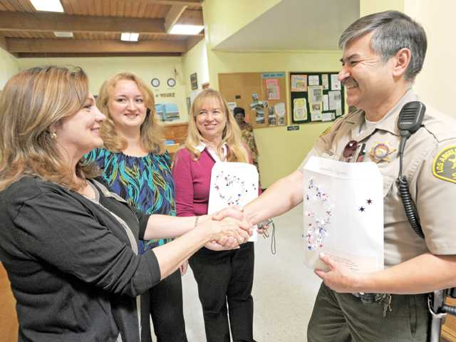 Deputy Joe Trejo of the Santa Clarita Valley Sheriff's Station, right, accepts an envelope of notes from, from left, Rachelle Dardeau, Lena Skiba and Robin Clough.