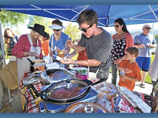 Sean Williams, center, samples some chili in a contest at a Patriot Day event presented by the Richard Rioux Park Senior Club held at Dr. Richard H. Rioux Memorial Park in Stevenson Ranch on Sunday.