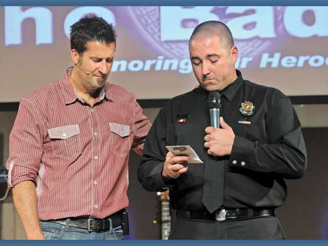 "Higher Vision Church pastor Jared Ming, left, prays with Pasadena Firefighter Matt Caffey as he tearfully reads ""The Firefighter's Prayer"" at the Behind the Badge event honoring first responders at Higher Vision Church  in Castaic on Sunday."