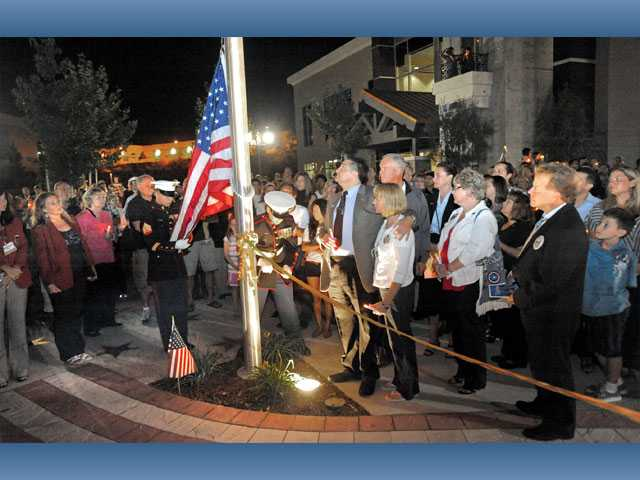 Hundreds of people in front of NorthPark Community Church watch as the U.S. flag is raised at the Honor Court dedication ceremony on Sunday.