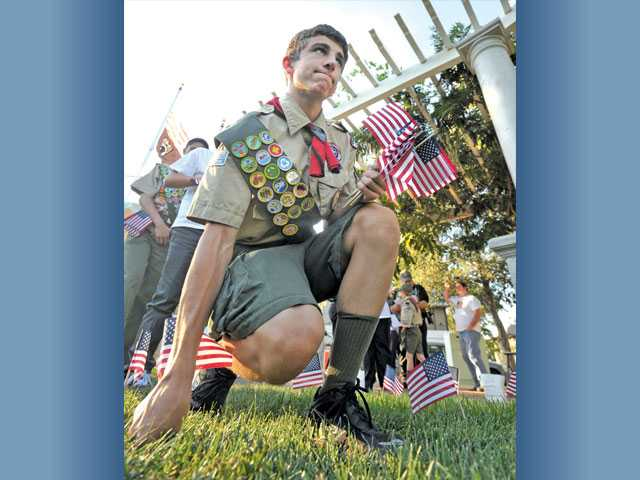 Boy Scout Luke Murphy, 14, of Troop 119 of Canyon Country, helps place 2,977 U.S. flags — one for each  person killed in the 9/11 attacks — at a memorial ceremony at Veterans Historical Plaza on Sunday in Newhall.