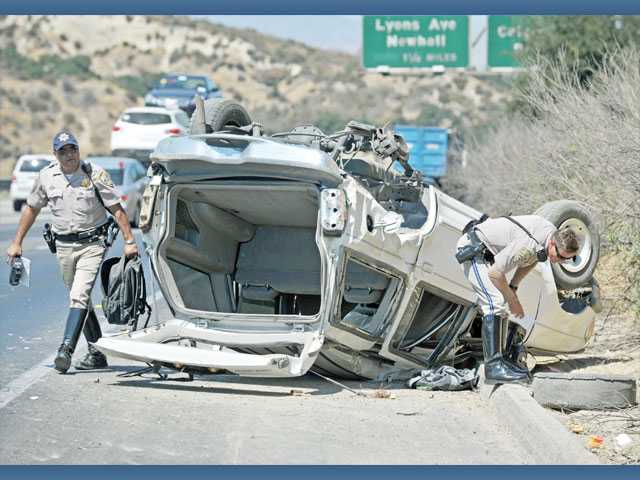 California Highway Patrol officers investigate the scene of a solo rollover crash involving a Ford Explorer on the shoulder of northbound Interstate 5 south of Calgrove Boulevard in Newhall on Monday afternoon.