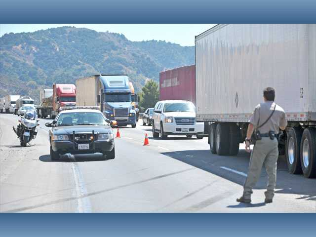 A California Highway Patrol officer directs traffic near an accident scene on northbound Interstate 5 south of Calgrove Boulevard in Newhall on Monday.