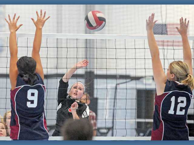Santa Clarita Christian's Logan Hermanson hits the ball past Trinity's Emily Kim, left, and Lizzie MacAdam on Wednesday at Legacy Volleyball Club in Valencia. SCCS won 3-2.