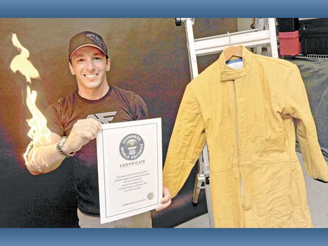 Jayson Dumenigo demonstrates a skin-burn stunt as he displays his Guinness World Records certificate for the longest full-body burn without oxygen alongside the suit he wore while he accomplished the feat at his Canyon Country home on Thursday.
