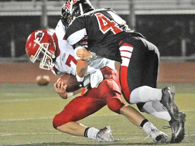Hart's Griffin Scott (44) sacks Burroughs quarterback Eli Peppmuller (7) in the second quarter on Thursday at Canyon High. Hart won the game 24-13.
