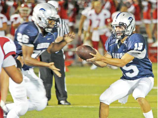 Saugus quarterback Jared Carbajal (15) hands off to Quentin Hendrix on Sept. 1 at Canyon High during the Centurions' 31-20 victory over Burroughs High.