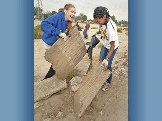 Ariana Nagainis, 14, left, and Olivia Bates, 13, from the Golden Valley High School Key Club break a piece of plywood to make it easier to handle.