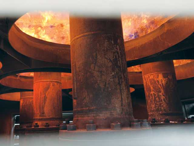 Burners are seen through the vents on a flare tower, which burns off excess methane gas.