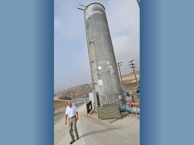Chiquita Canyon Landfill Division Vice President Mike Dean walks in front of a 50-foot-tall flare tower at the Ameresco Power Plant in the Chiquita Canyon Landfill in Castaic on Friday.