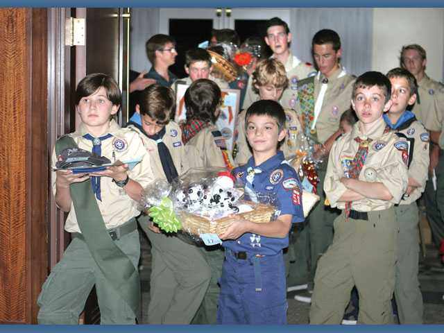 Scouts begin to circulate silent-auction items among event guests.