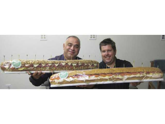 Robert Dorian, the local Togo's franchisee, left, and Aaron Ready, Togo's regional marketing manager, with the two, three-foot long Party Footer sandwiches that they delivered to the ravenous and grateful Signal staffers this past Tuesday.