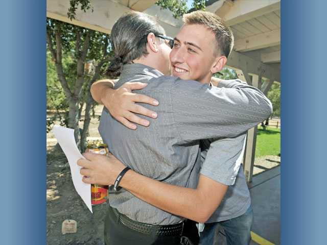ACTION Family Counseling founder Cary Quashen, left, gets a hug from Steven Cummings, right. Cummings, a heroin addict and resident at ACTION Family Counseling's Adult Ranch in Saugus, celebrated his 27th day of sobriety recently.