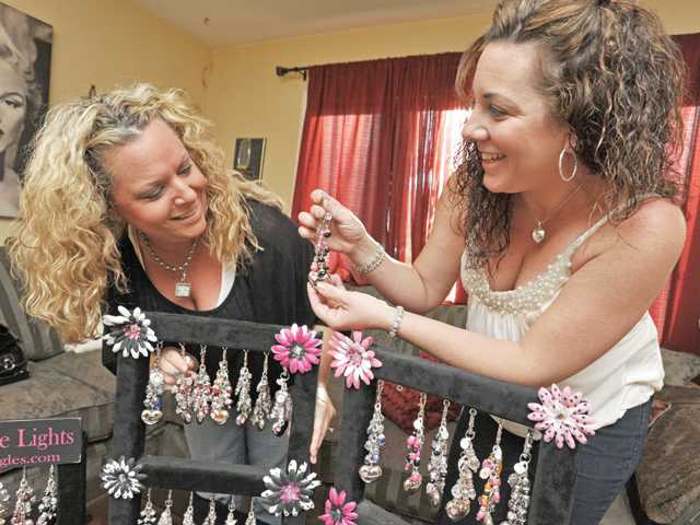 Tracy Abbatoye, left, and Julie Hahn look through their line of patent-pending Diva Dangles purse lights.