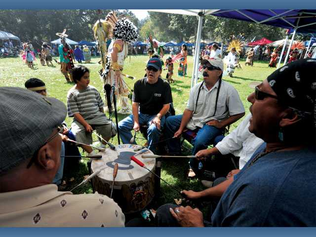 The Crooked Hat Singers beat the drums for the intertribal dance at the 18th annual Pow Wow at Hart Park.