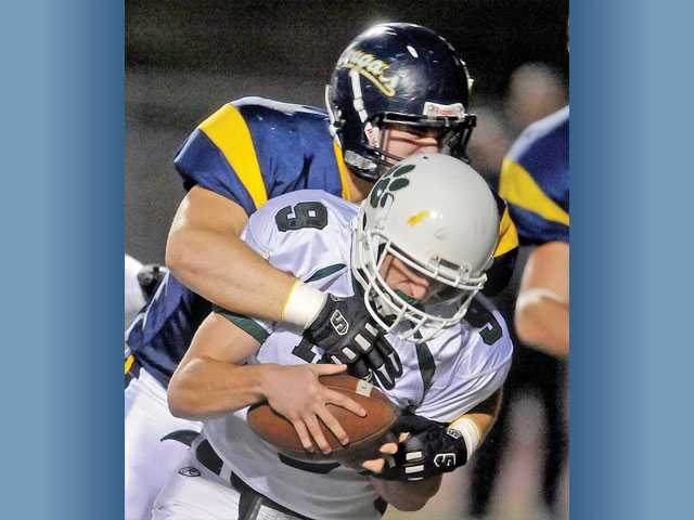 College of the Canyons defensive lineman Zach Eaton tackles East Los Angeles College quarterback Mike Oliver for a 5-yard loss during the first quarter on Saturday at Cougar Stadium. COC won the game 42-17.